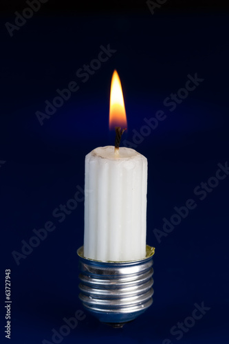 Light bulb fitting with no glass and candle standing on bright b