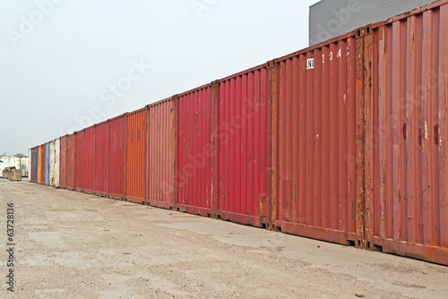 Row of red containers. Blue cloudy sky. Industrial environment.