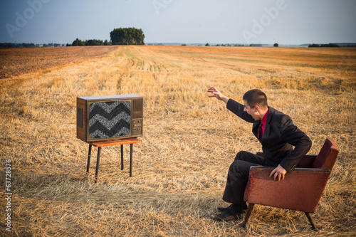 angry men with TV in summer field