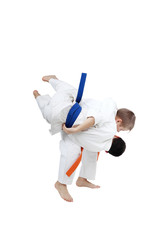 Boy with orange belt is doing throw a boy with blue belt