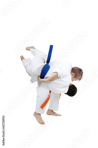 Boy with orange belt is doing throw a boy with blue belt