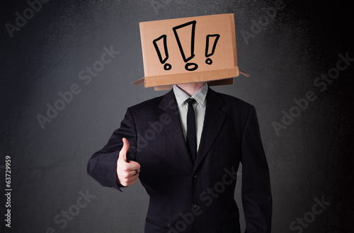 Businessman gesturing with a cardboard box on his head with excl