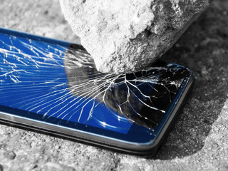 Cracked smartphone smashed by a stone (greyscale with blue)
