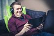Man relaxing on sofa watching movie on tablet with headphones