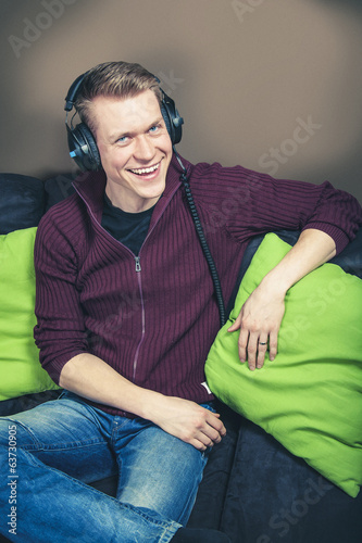 Man sitting on sofa listening music with headphones