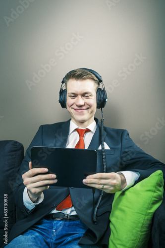 Business man on a break watching movie on tablet sitting on sofa