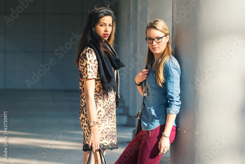 Couple of women portrait outdoors with modern buildings as backg