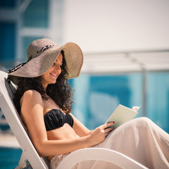 Young woman portrait relaxing and reading a book in swimming poo