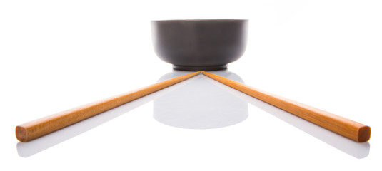 An empty bowl with a pair of chopsticks over white background