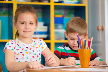 Two cute little girls drawing at school