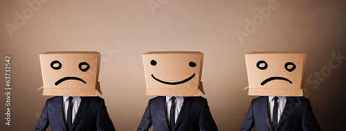 Handsome men in suit gesturing with drawn smiley faces on box