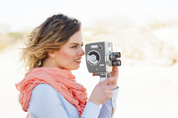 Outdoor Portrait of beautiful woman holding vintage 8mm camera