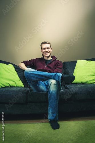 Man relaxing and sitting on sofa smiling