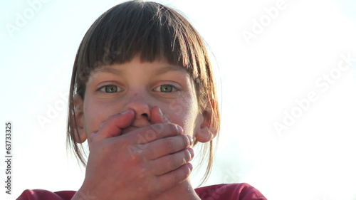 Boy closing mouth with hands