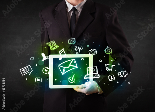 Person holding a tablet with media icons and symbols
