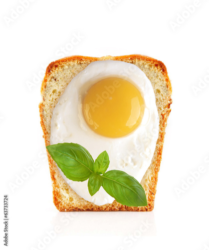 Scrambled eggs on bread with basil isolated on white