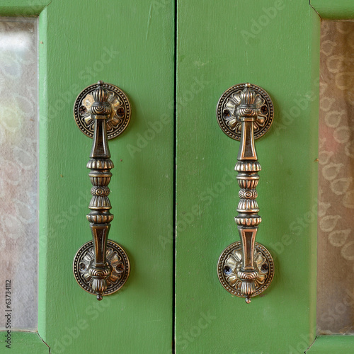 Door handle on green wooden door