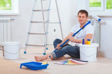 a handsome painter sitting on floor with paint tools holding pai