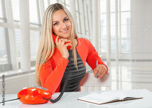 a young beautiful smiling caucasian businesswoman sitting at tab