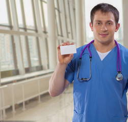 caucasian young doctor showing white vizit card and looking at c