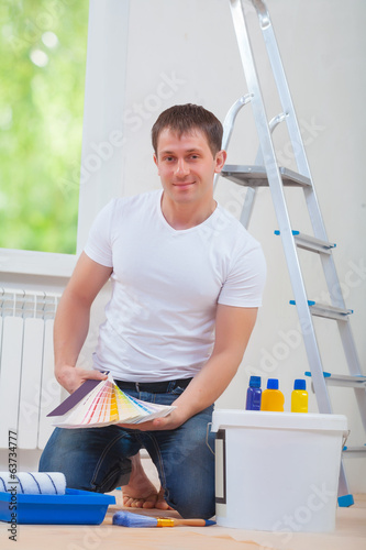 handsome young man sitting on floor with paint tools holdint col