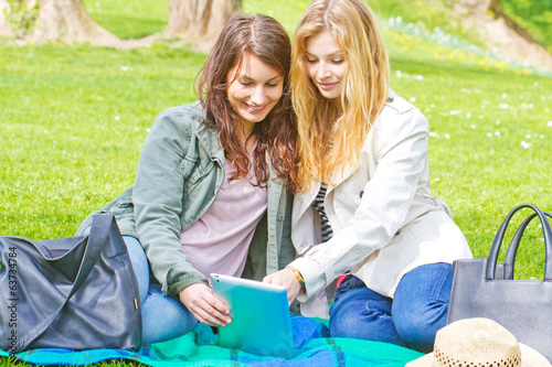 Two young women with tablet in parc