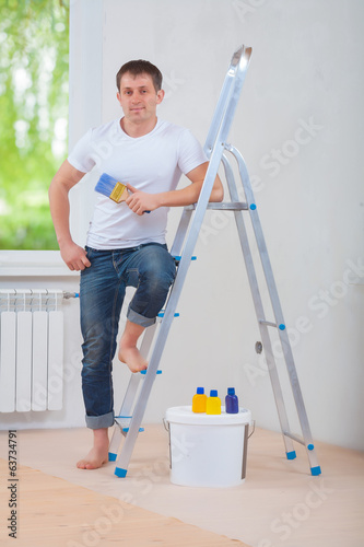 handsome young man standing near ladder holding paintbrush and l