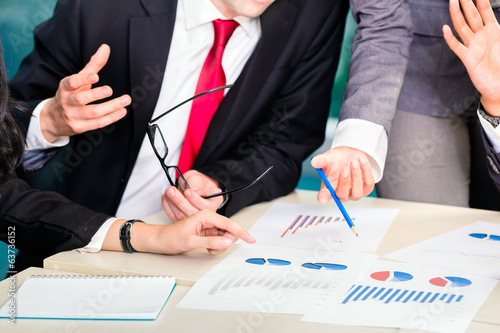 businesspeople anaylzing graph in office