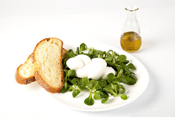 Treccia di mozzarella fresca con valeriana e fette di pane