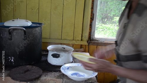 woman put potato dumplings with meat in boiling pot water stove