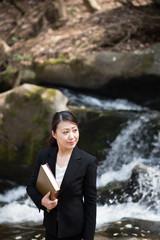 流れの急な川の近くで座って本を読むスーツの女性