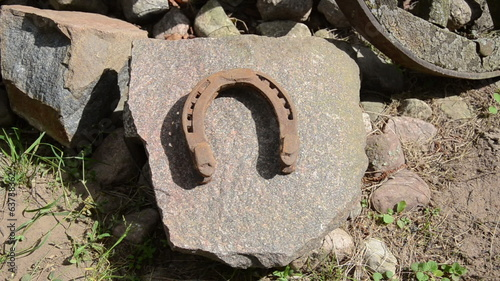 hand puts old iron horseshoes on large flat stone