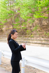 路上でタブレットを使っているアジアの女性ビジネスマン