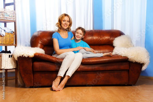 Mother and child sitting on couch at home