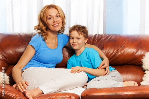 Happy mother cuddles son on couch