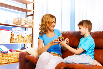 Boy gives gift to his mother on brown sofa