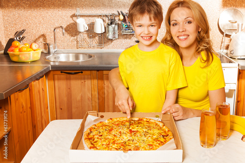 Happy child and mother slice pizza together