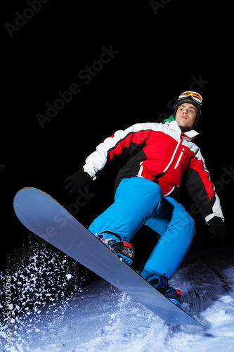 Portrait of snowboarder jumping at night