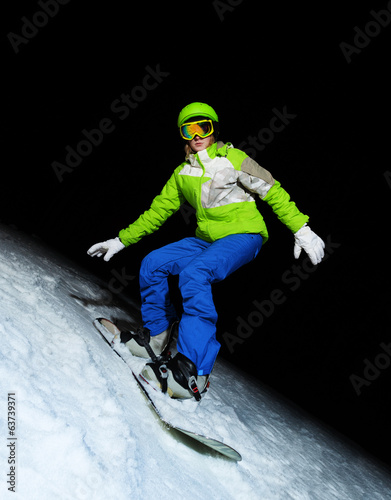 Young woman on snowboard at night