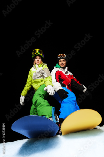 Man and woman standing on snowboards at night