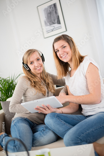 two cheerful young woman playing with a digital tablet
