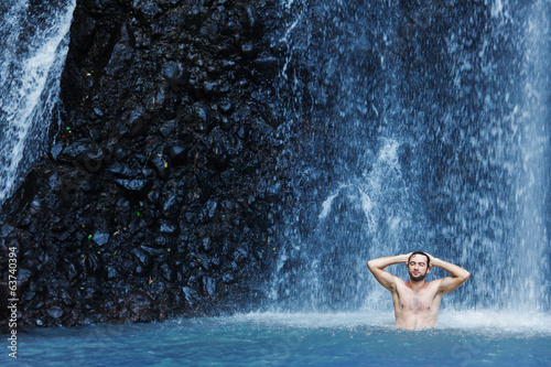 Handsome young man refreshing in waterfall in bali