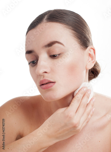 Woman with well-groomed complexion  holds cotton swab near her f