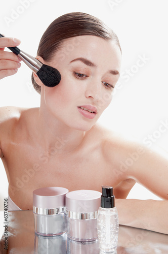 Young beautiful girl applying powder by brush on her face.