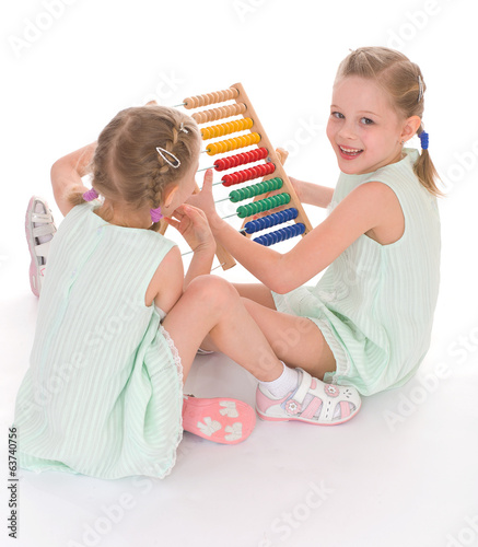 Cute sisters work in the Montessori environment.
