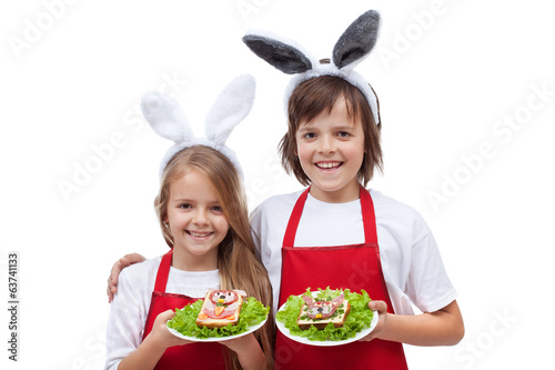 Happy chefs with bunny ears holding rabbit shaped sandwiches