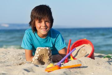 Boy building sand castles on the sea shore