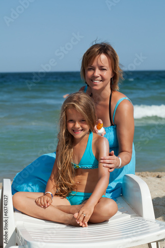 Woman and little girl using sunscreen cream