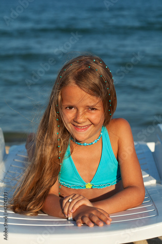 Little girl in bright sunshine at the seaside