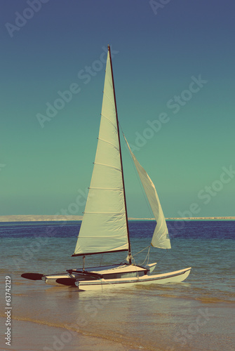 sailing catamaran on beach - vintage retro style